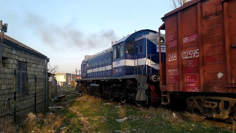 Тепловоз ТЭМ2 5043 едет между домами на станцию Баладжары