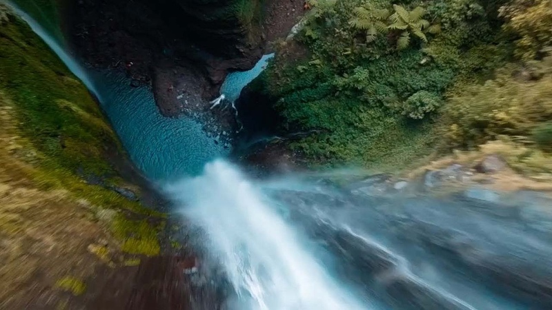 Drone Flies Through Jungle Waterfall