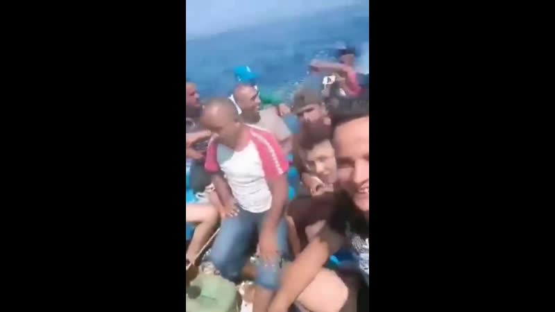 Happy Tunisian boat migrants making the 150 km trip across the Mediterranean Sea to Lampedusa